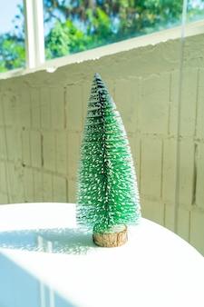 Kunststoff-weihnachtsbaum dekorieren auf dem tisch für weihnachten und ein frohes neues jahr-festival