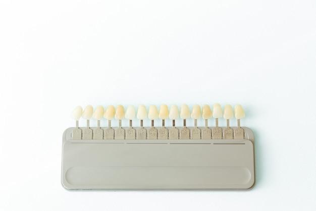 Kunststoff-zahnimplantat zur auswahl des farbtons der auf weiß isolierten zähne