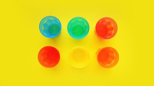 Kunststoffglas verschiedener farben isoliert auf gelber oberfläche - helles sommerkonzept für design und banner