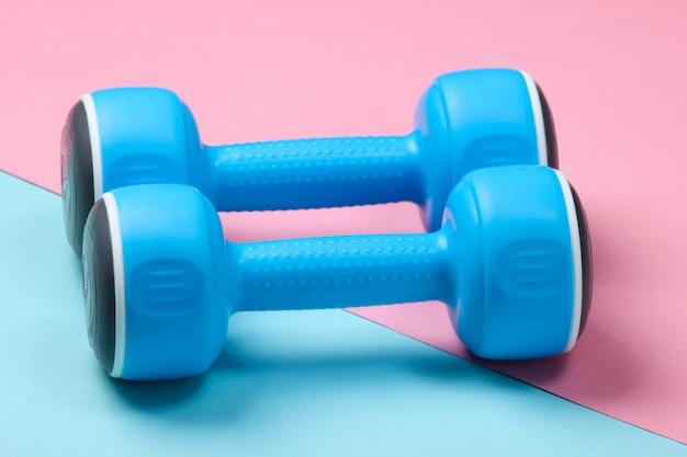 Kunststoffhanteln auf einem blau-rosa pastell.