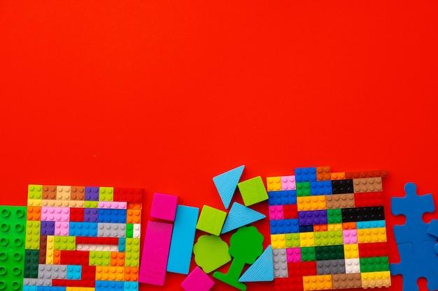 Kunststoffkonstrukteurdetails auf rotem hintergrund schließen oben