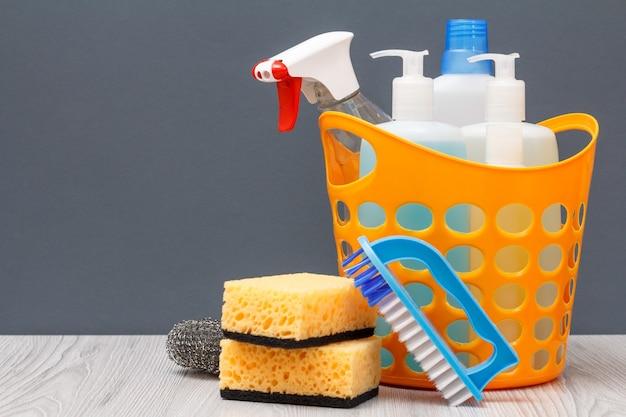 Kunststoffkorb mit flaschen spülmittel, glas- und fliesenreiniger, reinigungsmittel für mikrowellenherde und herde. brushe und schwämme auf grauem hintergrund. wasch- und reinigungskonzept.