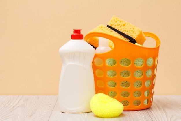 Kunststoffkorb mit schutzhandschuh, flaschen mit spülmittel, glas- und fliesenreiniger, reinigungsmittel für mikrowellenherde und herde, schwämme auf beigem hintergrund. wasch- und reinigungskonzept.