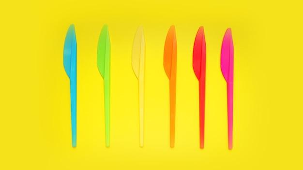 Kunststoffmesser violett, orange, gelb, blau, rot isoliert auf gelber oberfläche - helles sommerkonzept für design und banner