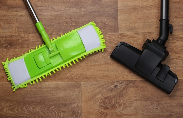Kunststoffmop und staubsaugerkopf auf holzboden. desinfektion und reinigung im haus. draufsicht