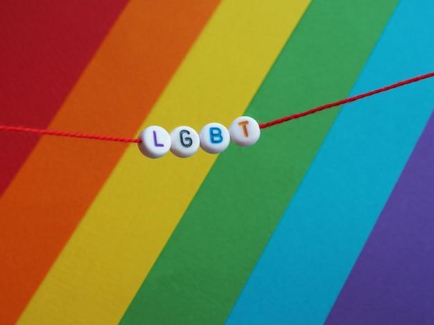 Kunststoffperlen mit buchstaben lgbt auf einem roten faden auf dem hintergrund der regenbogenfahne