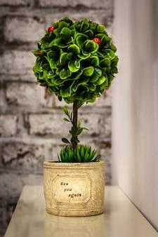 Kunststoffpflanze, busch auf weißem tisch mit backsteinmauerhintergrund
