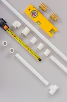 Kunststoffrohre für das wassersystem, lineal und messebene auf grauem hintergrund. reparaturservice, verkauf, online. flach liegen. platz kopieren.