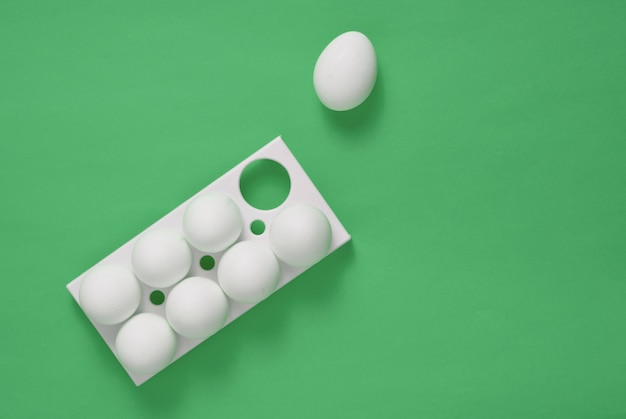 Kunststoffschale mit weißen eiern und auf einem grünen pastellhintergrund