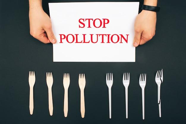 Kunststoffverschmutzungskonzept. plastik frei. hände halten papier mit worten stop pollution in der nähe von umweltfreundlichen null-abfall- und einweggabeln. gabeln sind in der reihe auf dunklem hintergrund, draufsicht.