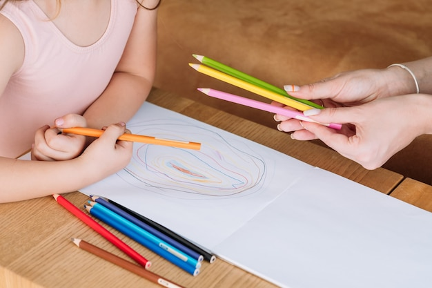 Kunsttherapie für kinder. kleine mädchenhand, die einen bleistift nimmt, um zu beginnen, ein bild zu zeichnen. kinder künstlerische freizeit und kreative malerei hobby.