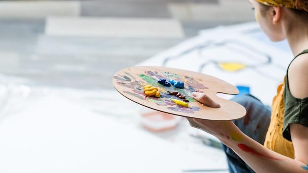 Kunsttherapie und freizeit. beschnittener schuss der dame unter verwendung der acrylfarbpalette, die kunstwerke schafft