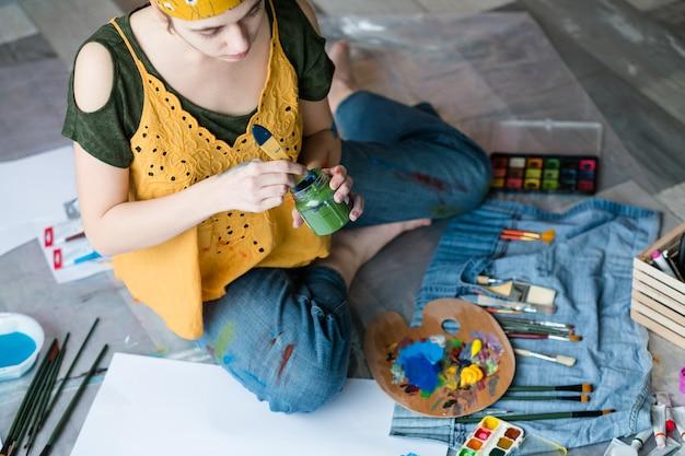 Kunsttherapie und freizeit. draufsicht der dame, die auf boden sitzt und malt genießt