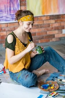 Kunsttherapie und freizeit. kreative junge malerin, die auf boden sitzt und pinsel wäscht