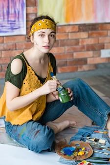 Kunsttherapie und freizeit. kreativer junger weiblicher maler, der auf boden sitzt