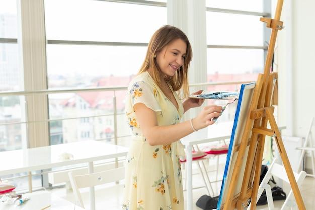 Kunstunterricht, zeichen- und kreativitätskonzept - studentin sitzt vor staffelei mit palette und pinsel