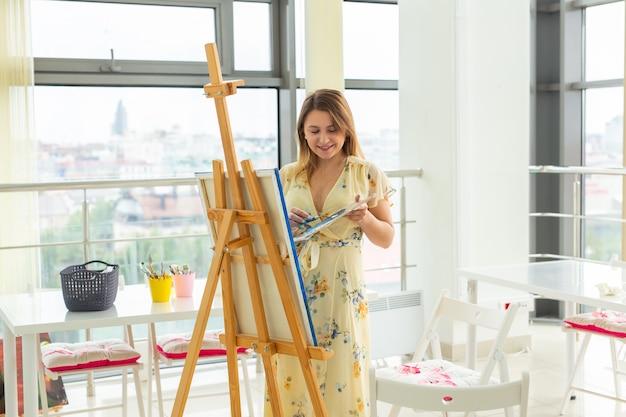Kunstunterricht, zeichnung und kreativitätskonzept - studentin sitzt vor staffelei mit palette und pinsel.