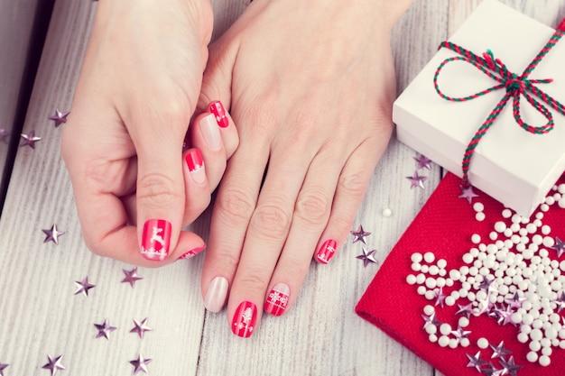 Kunstweihnachtsmaniküre auf weiblichen händen. bild auf weißem holzhintergrund mit geschenk und verstreuten kleinen hellen sternen