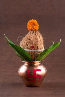 Kupfer kalash mit kokos- und mangoblatt mit blumendekor auf einem holztisch. essentiell in der hinduistischen puja.