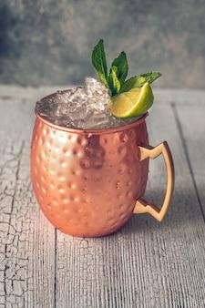 Kupferbecher mit moscow mule cocktail garniert mit minze und limette
