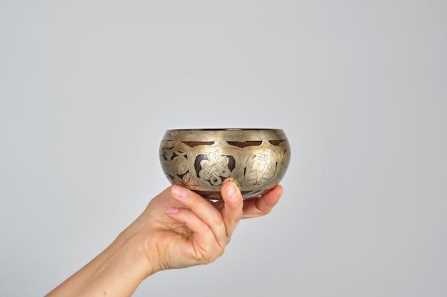 Kupferne gesangschüssel in der weiblichen hand