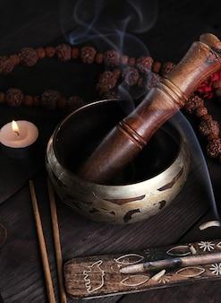 Kupferne klangschale und ein holzstab auf einem braunen tisch