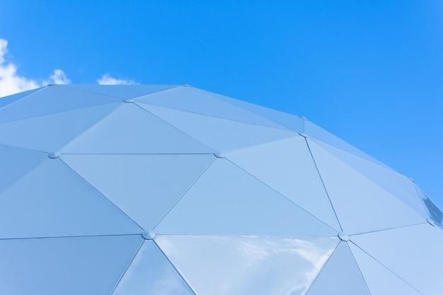 Kuppel bestehend aus dreieckigen stücken des schutzabschnitts auf dem himmelhintergrund.