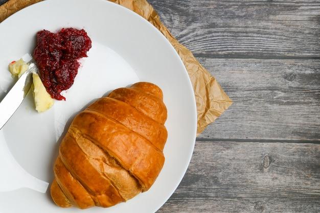 Kurasan mit butter und marmelade. der anfang des morgens. eine tasse kaffee. frisches französisches croissant. kaffeetasse und frisch gebackene croissants auf einem holz. .
