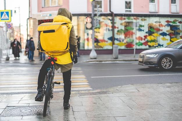 Kurier auf fahrrad liefert leckeres essen in den straßen der stadt b