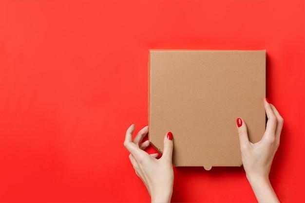 Kurier, der pizzakasten in den händen lokalisiert auf rotem hintergrund hält