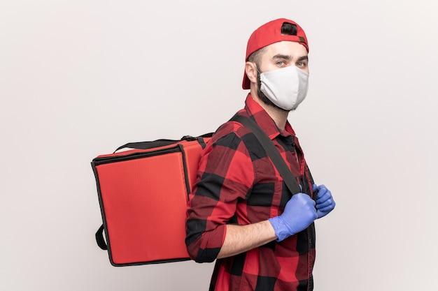 Kurier des cafés oder restaurants in arbeitskleidung und schutzmaske und handschuhen, die eine große rote tasche auf dem rücken tragen, während sie lebensmittel an kunden liefern
