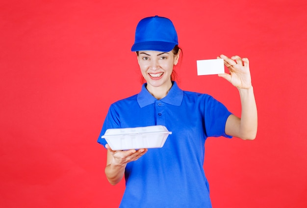 Kurier frau, die eine weiße box zum mitnehmen hält und ihre visitenkarte vorlegt.