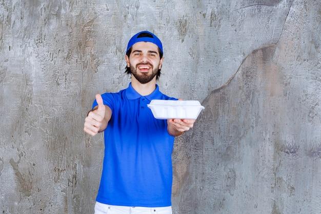 Kurier in blauer uniform, der eine plastikbox zum mitnehmen hält und ein positives handzeichen zeigt