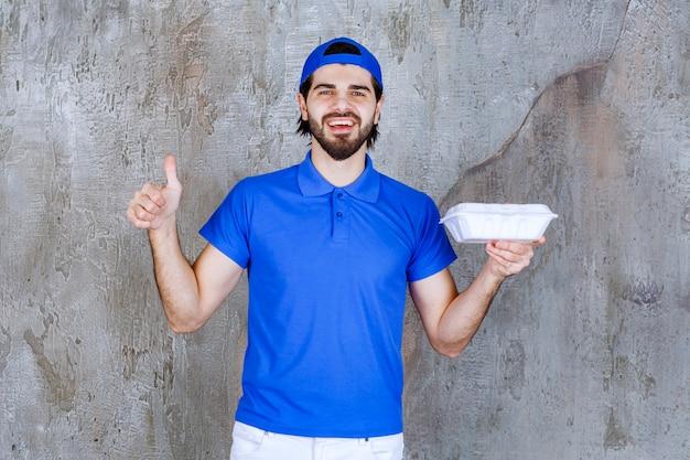 Kurier in blauer uniform, der eine plastikbox zum mitnehmen hält und ein positives handzeichen zeigt.