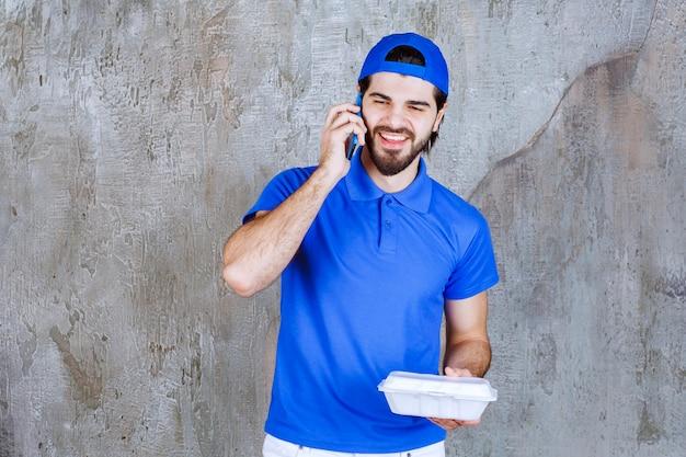 Kurier in blauer uniform, der eine plastikbox zum mitnehmen hält und neue bestellungen per telefon entgegennimmt.