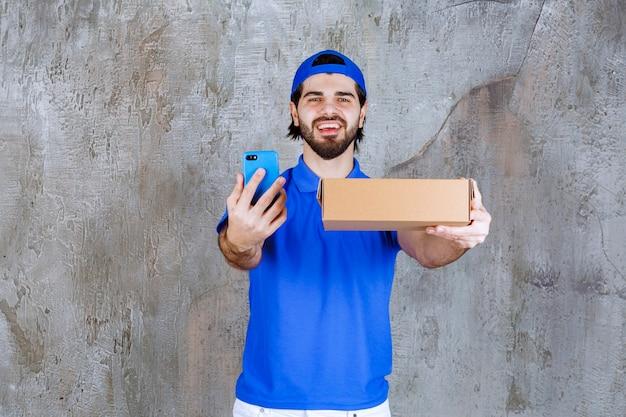 Kurier in blauer uniform hält eine box zum mitnehmen und macht einen videoanruf