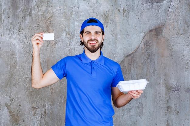 Kurier in blauer uniform hält eine plastikbox zum mitnehmen und präsentiert seine visitenkarte.