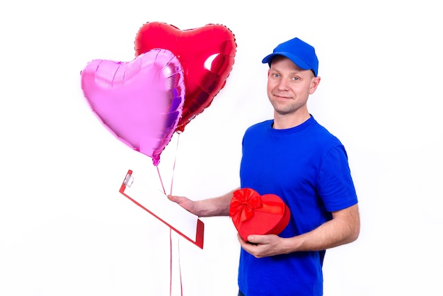 Kurier in blauer uniform hält rote herzförmige geschenkbox und ballon zum valentinstag. zuhause