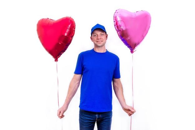 Kurier in blauer uniform hält rote herzförmige geschenkbox und ballon zum valentinstag.