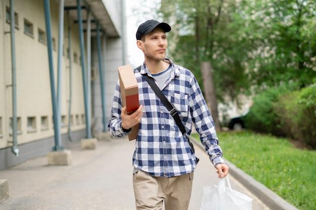 Kurier in eile laufen, um ein paket und eine schachtel in der stadt zu liefern