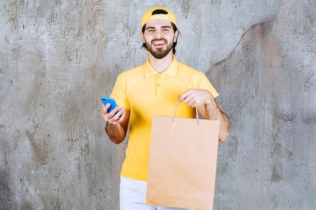 Kurier in gelber uniform, der eine einkaufstüte aus pappe hält und mit dem telefon spricht