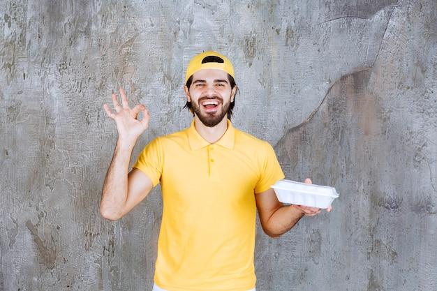 Kurier in gelber uniform, der eine plastikbox zum mitnehmen liefert und ein positives handzeichen zeigt