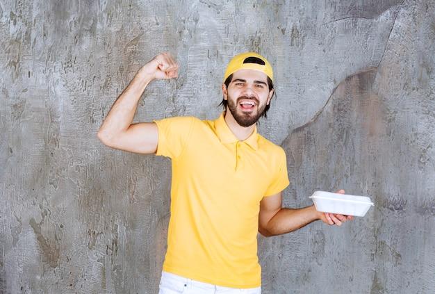 Kurier in gelber uniform, der eine plastikbox zum mitnehmen liefert und ein positives handzeichen zeigt.