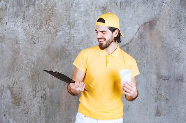 Kurier in gelber uniform, der einen einwegbecher hält und die kundenliste liest