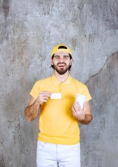 Kurier in gelber uniform, der einen einwegbecher hält und visitenkarte vorstellt.
