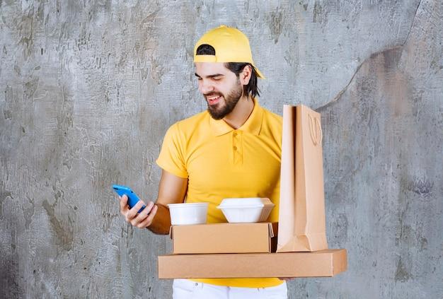 Kurier in gelber uniform, der pakete und einkaufstasche zum mitnehmen hält und einen videoanruf tätigt.