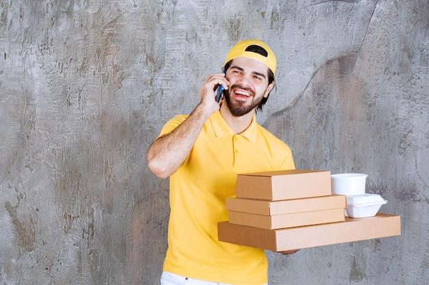 Kurier in gelber uniform, der pakete und einkaufstasche zum mitnehmen hält und neue bestellungen per telefon entgegennimmt oder einfach nur spricht.