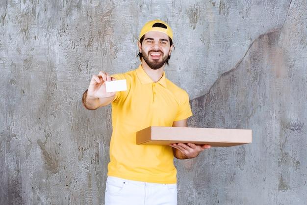 Kurier in gelber uniform hält eine pizzaschachtel zum mitnehmen und präsentiert seine visitenkarte
