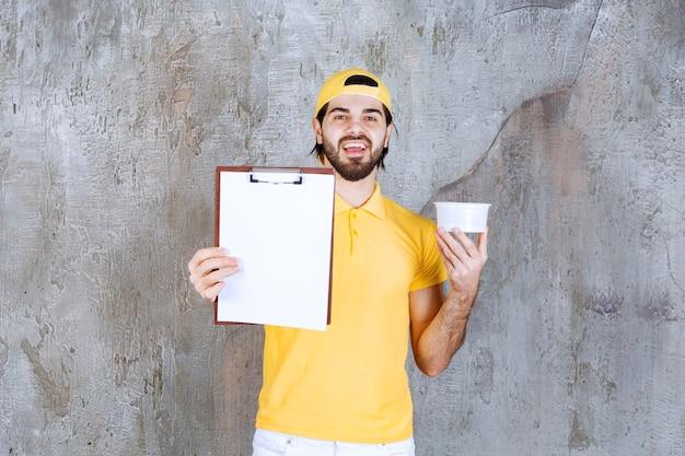 Kurier in gelber uniform hält einen plastikbecher und bittet um eine unterschrift