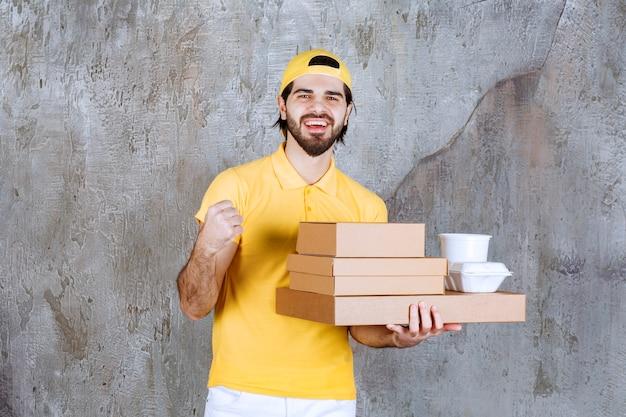 Kurier in gelber uniform hält pakete und kartons zum mitnehmen und zeigt positives vorzeichen